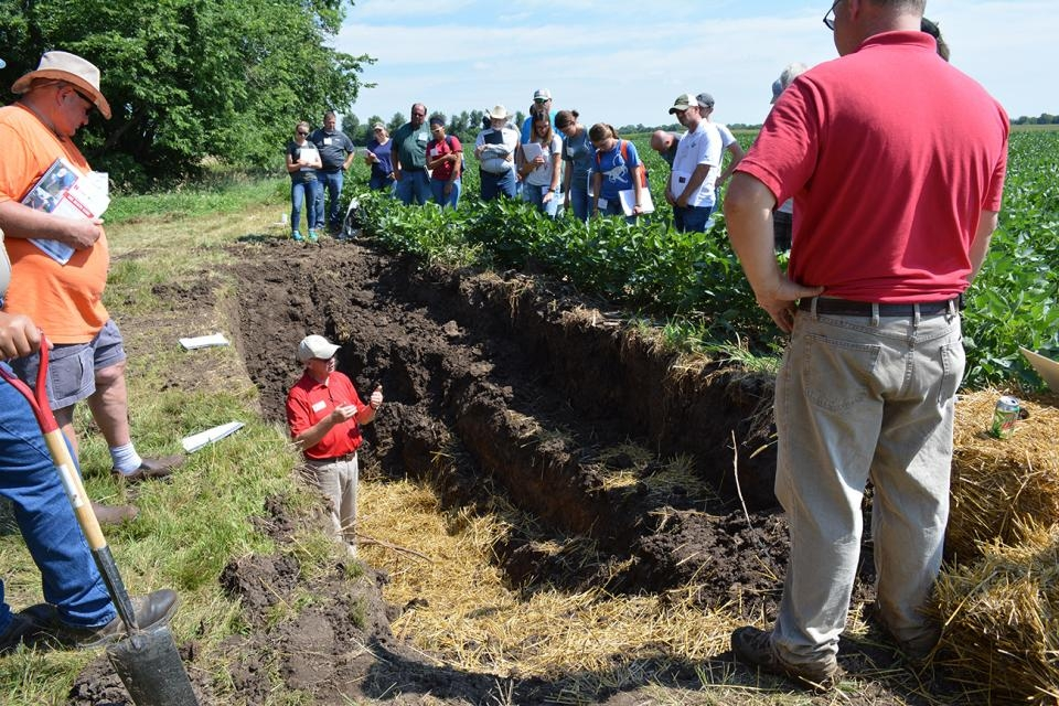 Instructor in a ditch explaining soil health to participants